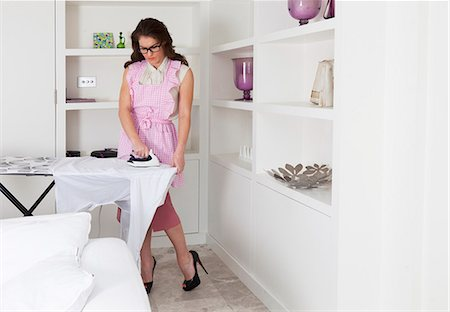 Young woman ironing shirt Stock Photo - Premium Royalty-Free, Code: 649-07239837