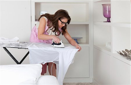Young woman bending forwards ironing shirt Stock Photo - Premium Royalty-Free, Code: 649-07239838