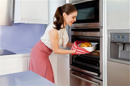 Young woman taking roasting dish out of oven Stock Photo - Premium Royalty-Free, Code: 649-07239849