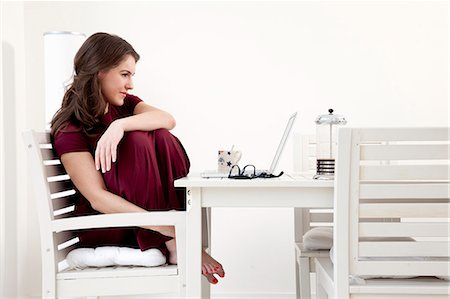 red chair - Young woman sitting at table with laptop Stock Photo - Premium Royalty-Free, Code: 649-07239842