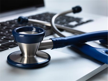 selective focus computer no people - Stethoscope sitting on laptop illustrating online healthcare and doctor's desk Stock Photo - Premium Royalty-Free, Code: 649-07279535