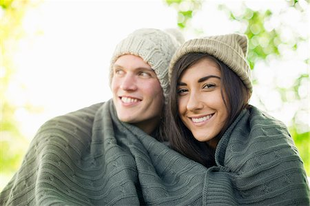 Young couple wearing knit hats wrapped in blanket Stock Photo - Premium Royalty-Free, Code: 649-07279649