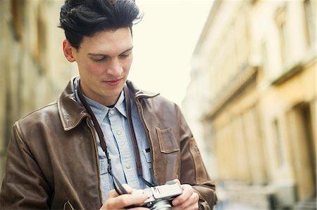 Young man holding camera Stock Photo - Premium Royalty-Free, Code: 649-07279660