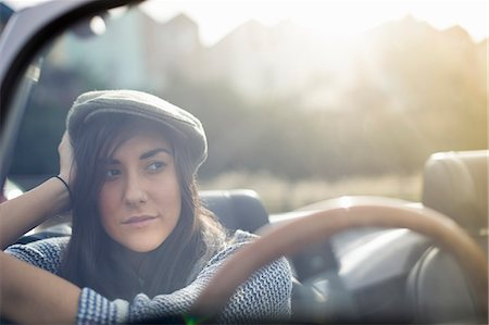 portrait looking away - Young woman wearing flat cap in convertible Stock Photo - Premium Royalty-Free, Code: 649-07279670