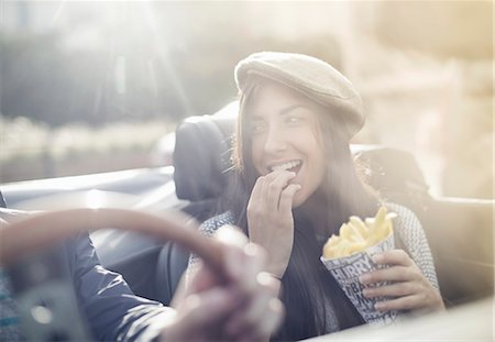 Young couple in convertible, woman eating chips Stock Photo - Premium Royalty-Free, Code: 649-07279672