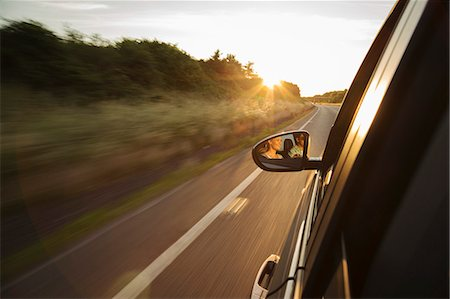 Car driving along road, reflection in wing mirror Stock Photo - Premium Royalty-Free, Code: 649-07279931