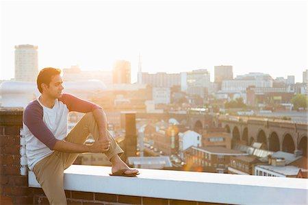 portrait looking away - Man sitting on wall on rooftop, Birmingham, England, UK Stock Photo - Premium Royalty-Free, Code: 649-07279955