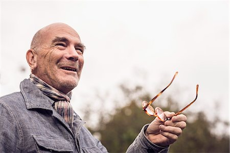 Senior man gesturing with spectacles Stock Photo - Premium Royalty-Free, Code: 649-07279998