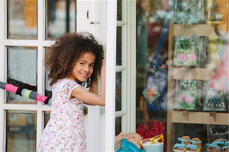 Happy young girl standing outside shop Stock Photo - Premium Royalty-Free, Code: 649-07280003