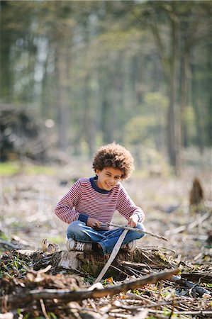 Portrait of boy sitting on tree stump with sticks Stock Photo - Premium Royalty-Free, Code: 649-07280012