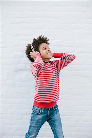 Boy on street happily listening to headphones Stock Photo - Premium Royalty-Free, Code: 649-07280034