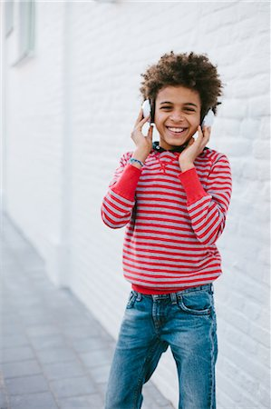 Portrait of boy on street happily listening to headphones Stock Photo - Premium Royalty-Free, Code: 649-07280035