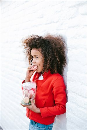 sweets - Young girl leaning against wall eating macaroons Stock Photo - Premium Royalty-Free, Code: 649-07280042