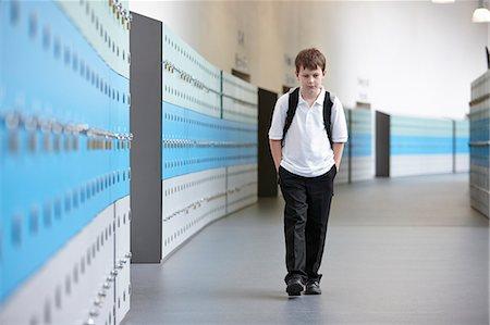 Unhappy schoolboy walking alone in school corridor Stock Photo - Premium Royalty-Free, Code: 649-07280056