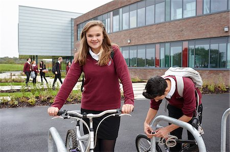 Teenagers unlocking cycles outside school Stock Photo - Premium Royalty-Free, Code: 649-07280051