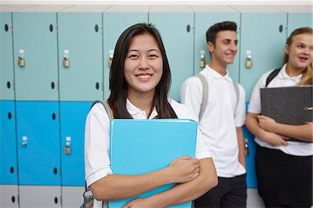 Portrait of teenage schoolgirl next to lockers Stock Photo - Premium Royalty-Free, Code: 649-07280068