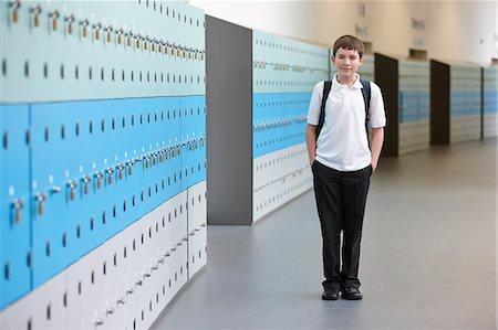 Portrait of schoolboy with hands in pockets in school corridor Stock Photo - Premium Royalty-Free, Code: 649-07280063