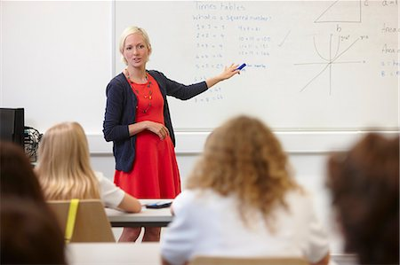 Female teacher using white board in front of class Stock Photo - Premium Royalty-Free, Code: 649-07280098
