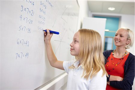 school work - Schoolgirl doing multiplication on white board Stock Photo - Premium Royalty-Free, Code: 649-07280099