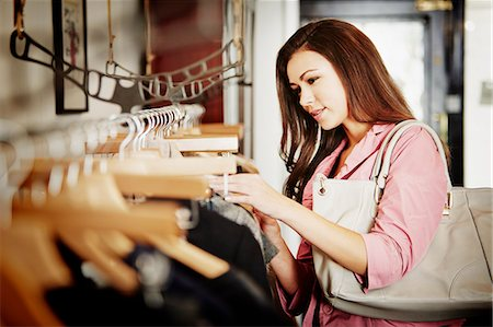 Young woman looking at selection of clothes on clothes rail Stock Photo - Premium Royalty-Free, Code: 649-07280204