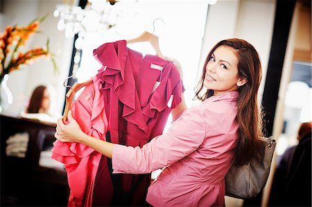 decision - Young woman looking pink top on hanger Stock Photo - Premium Royalty-Free, Code: 649-07280206