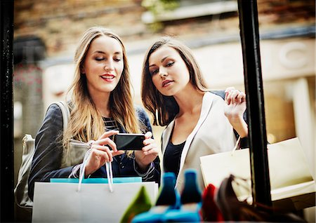 self indulgence - Young women window shopping, taking photograph with smartphone Stock Photo - Premium Royalty-Free, Code: 649-07280217