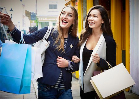 fashion - Young women arm in arm, carrying shopping bags down street Stock Photo - Premium Royalty-Free, Code: 649-07280218