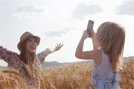 Girl taking photograph of mother in wheat field with arms open Stock Photo - Premium Royalty-Free, Code: 649-07280286