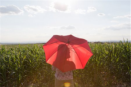 Woman standing holding red umbrella Stock Photo - Premium Royalty-Free, Code: 649-07280317