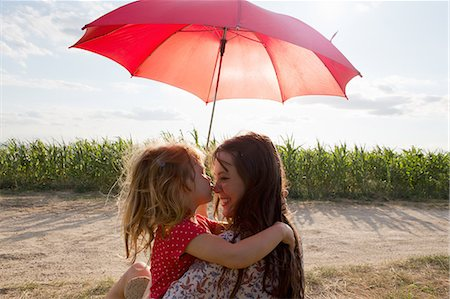 Mother and daughter hugging under red umbrella Stock Photo - Premium Royalty-Free, Code: 649-07280321