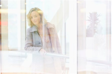 people on mall - Mid adult woman peering through shopping centre window Stock Photo - Premium Royalty-Free, Code: 649-07280400