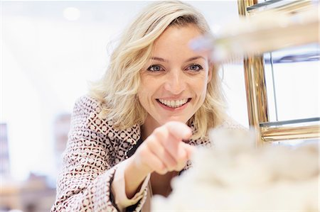 self indulgence - Mid adult female pointing at cake display in cafe Stock Photo - Premium Royalty-Free, Code: 649-07280418