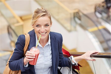 shopping mall - Businesswoman on escalator with shopping and fruit drink Stock Photo - Premium Royalty-Free, Code: 649-07280428