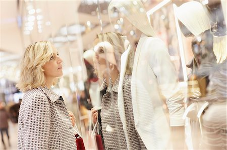 Mid adult female shopper looking at display window in shopping centre Stock Photo - Premium Royalty-Free, Code: 649-07280421
