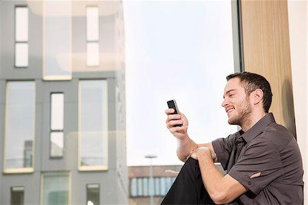 Businessman sitting on windowsill using smartphone Stock Photo - Premium Royalty-Free, Code: 649-07280452