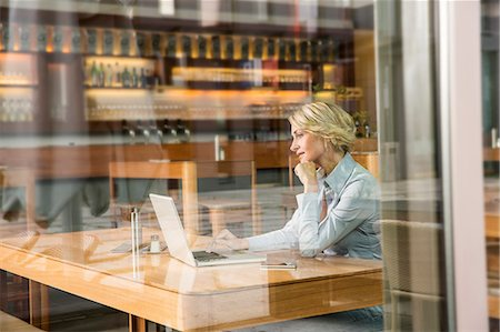 Businesswoman using laptop, view through window Stock Photo - Premium Royalty-Free, Code: 649-07280479