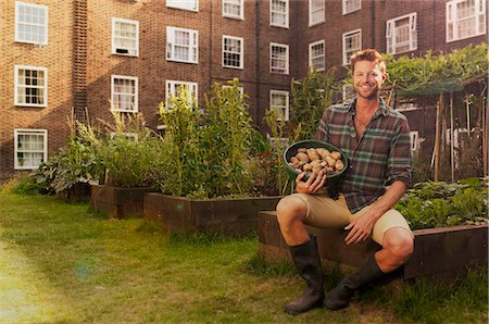 Mid adult man on council estate allotment with bowl of potatoes Stock Photo - Premium Royalty-Free, Code: 649-07280488