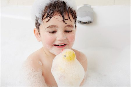 Boy in bath with bubbles on his head, holding rubber duck Stock Photo - Premium Royalty-Free, Code: 649-07280692