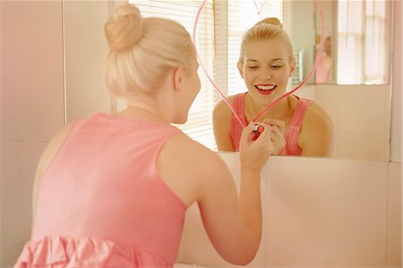 femininity - Young woman in bathroom drawing heart shape on mirror with lipstick Stock Photo - Premium Royalty-Free, Code: 649-07280715