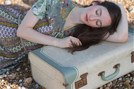 femininity - Portrait of young woman lying with suitcase on beach, Whitstable, Kent, UK Stock Photo - Premium Royalty-Free, Code: 649-07280794