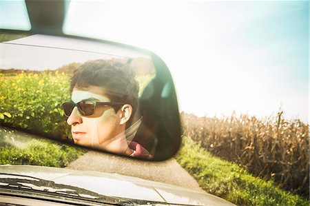 Mirror reflection of young man leaning driving on country road Stock Photo - Premium Royalty-Free, Code: 649-07280822