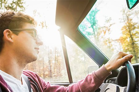 Young man leaning driving convertible on country road Stock Photo - Premium Royalty-Free, Code: 649-07280823