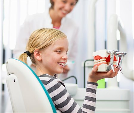 dentistry - Girl in dentists chair holding false teeth Stock Photo - Premium Royalty-Free, Code: 649-07280857