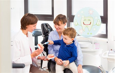dentistry - Dentist teaching boy on mothers lap how to brush teeth Stock Photo - Premium Royalty-Free, Code: 649-07280859