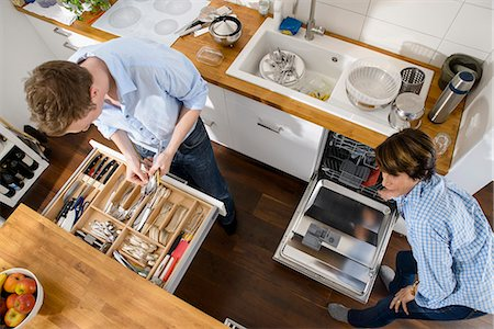 Grandmother and adult grandson tidying away cutlery from dishwasher Stock Photo - Premium Royalty-Free, Code: 649-07280945