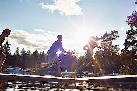 Three adult friends running along pier, Gavle, Sweden Stock Photo - Premium Royalty-Free, Code: 649-07280971
