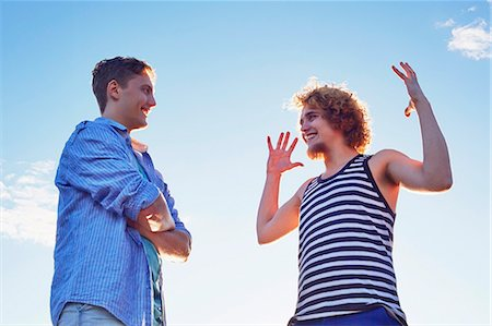 story - Two male friends enjoying conversation in sunlight Stock Photo - Premium Royalty-Free, Code: 649-07280973