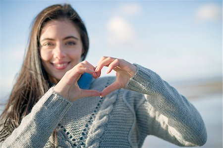sweater - Young woman making heart shape with hands Stock Photo - Premium Royalty-Free, Code: 649-07281024