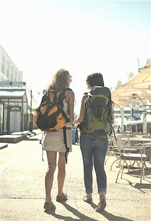 Rear view of woman walking along street carrying backpacks Stock Photo - Premium Royalty-Free, Code: 649-07436327