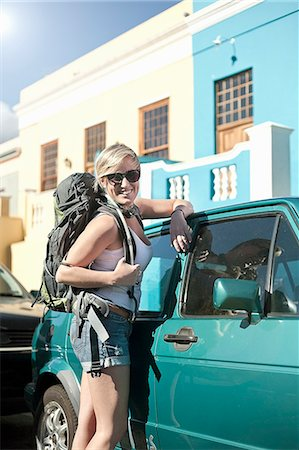 Young woman carrying backpack, leaning against car Stock Photo - Premium Royalty-Free, Code: 649-07436320